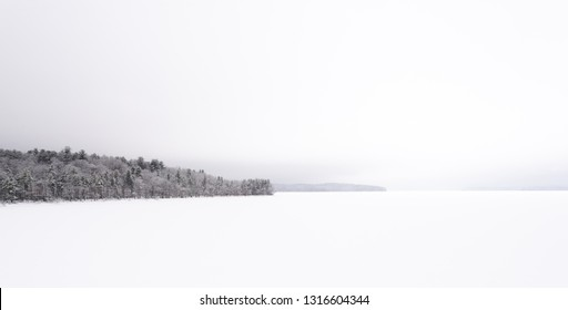 Ashokan Reservoir, Tourist Destination in Upstate NY. Part of the NYC Water Supply. Winter Scene During a Snowstorm. Snow covered Reservoir and Trees in Whiteout Conditions. Tranquil Panorama.