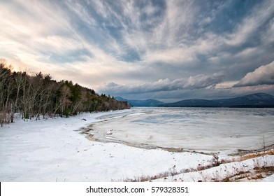 Ashokan Reservoir winter scene with dramatic sky, mountains, snow and ice. Ashokan reservoir provides water to New York City. It is located in the Mid-Hudson Valley of NY.