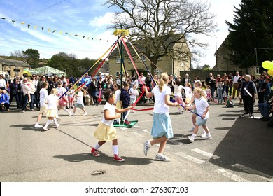 ASHOVER, DERBYSHIRE, UK. MAY 04, 2015.  Young girls dancing the Maypole at the village carnival at Ashover in Derbyshire, UK.