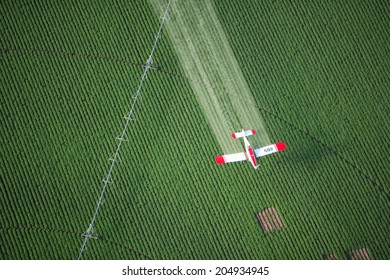 Ashton, Idaho, USA July 8, 2009 An overhead view of a crop duster spraying chemicals on green farmland.