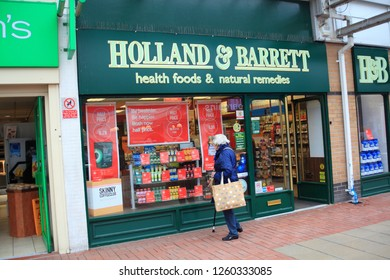 Ashton-Under-Lyne Lancashire UK 06.03.2018 An elderly lady looking in the store front window of the health shop Holland & Barret
