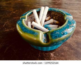 Ashtray and cigarette stub. Ashtray with cigarette butt inside.