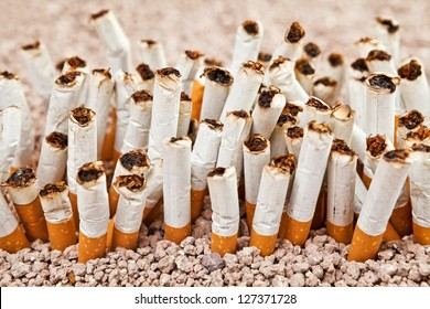 Ashtray full of smoked cigarettes in the sand disposed as a wall