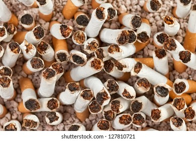 Ashtray full of smoked cigarettes in the sand closeup from above