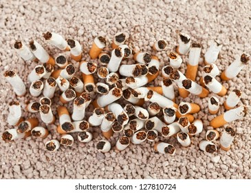 Ashtray full of smoked cigarettes in the sand arranged as a rectangle