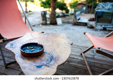 Ashtray on a wooden table. Ashtray with cigarette butts. Coffee table in the yard.