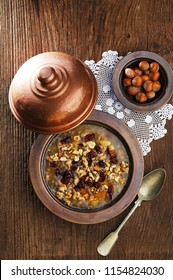 Ashure, ashura, asure, traditional Turkish dessert, in an authentic copper plate, rustic table