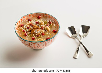 Ashure (Noah's Pudding) Traditional Turkish, Islamic dessert in a colorful bowl with two spoons on white background