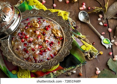 Ashure (Noah's Pudding) Traditional Turkish Islamic dessert in a silver traditional plate on wooden table with pomegranate, autumn leaves and silver spoon