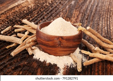 Ashwagandha ground powder and root in wooden bowl on brown wooden table.