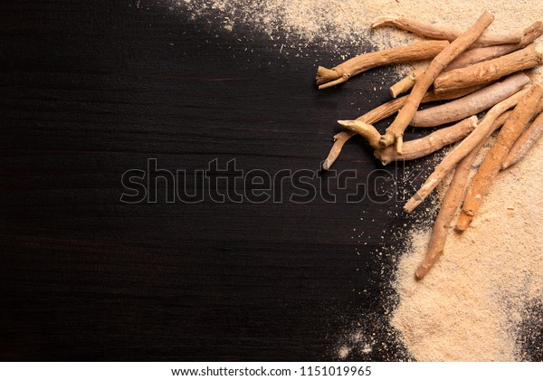 Ashwagandha powder and roots on black background with copy space. Superfood, adaptogen, nutritional supplement.