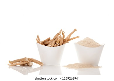 Ashwagandha powder and roots in white cups isolated on white background.