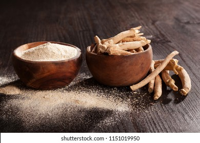 Ashwagandha powder and roots in wooden cups on black background. Superfood, adaptogen, nutritional supplement.