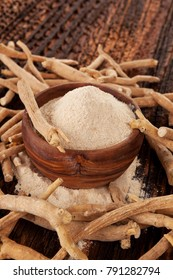 Ashwagandha powder in wooden bowl with Ashwagandha roots on wooden table.
