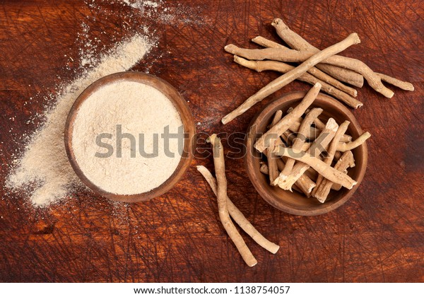 Ashwagandha root and powder in bowl on wooden backgroud, top view. Adaptogen, medicinal plant.