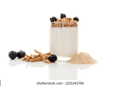 Ashwagandha root and powder with yogurt, fruit and muesli isolated on white background. Adaptogenic nutritional supplement, withania somnifera.