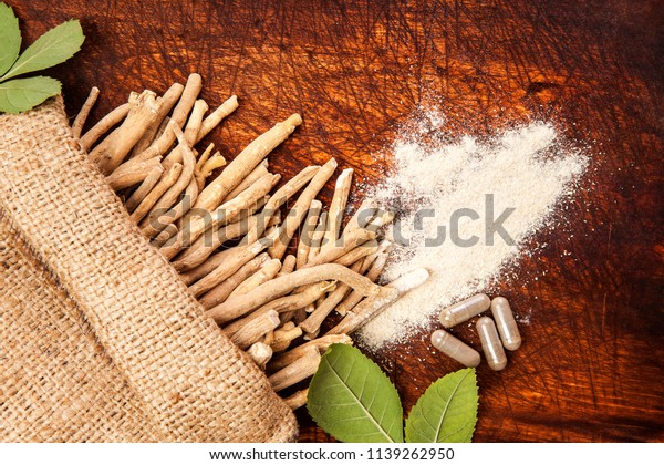 Ashwagandha roots with powder and gel capsules from above.
