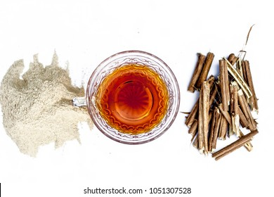 Ashwagandha roots and its powder also known as Indian ginseng, isolated on white essential beneficial for hair loss with its organic tea made from its powder.