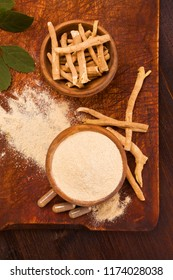 Ashwagandha superfood powder and root on cutting board on wooden table.