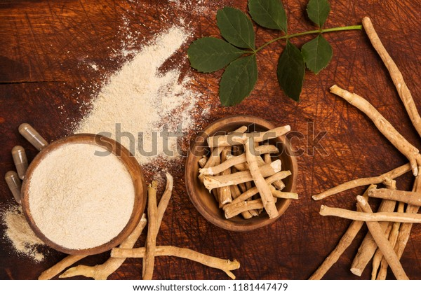 Ashwagandha superfood powder and root on cutting board on wooden table from above. Adaptogen.