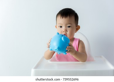 Asia baby boy saving money for future concept on white background, Happy baby with a piggy bank