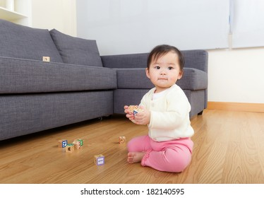Asia baby girl play with toy block at home