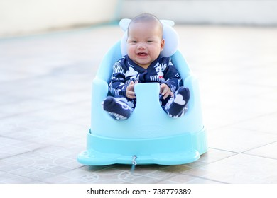 Asia baby sitting in a blue seat.