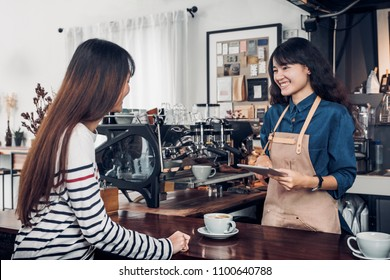Asia Barista waiter take order from customer in coffee shop,cafe owner writing drink order at counter bar,Food and drink business concept,Service mind concept