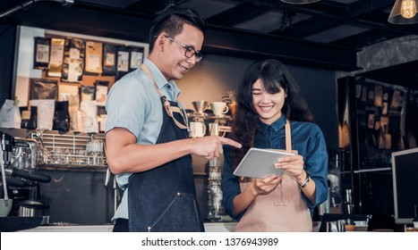 Asia Barista waiter take order from customer in coffee shop,cafe owner writing drink order at counter bar,Food and drink business concept,Service mind concept.restaurant worker