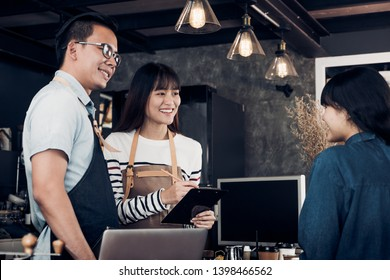 Asia barista waiter and waitress take order from customer in coffee shop,Two cafe owner writing drink order at counter bar,Food and drink business concept,Service mind concept