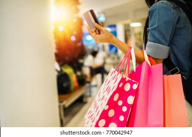 Asia beautiful woman carrying shopping bag and walking in the department store.young lady shopping by using credit card on weekend.