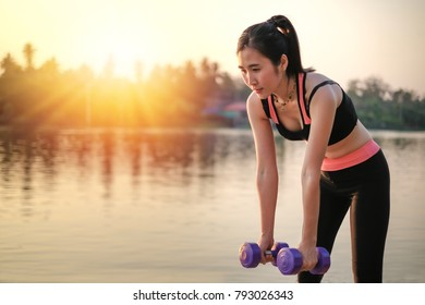 Asia beautiful woman exercise by lifting weight in sexy sport wear near the river when sunset.