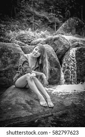 Asia Beautiful young girl sitting on the stone in water fall, black and white image