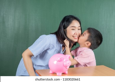 Asia Boy and His Mother with Piggy bank on table and Chalkboard.Child Saving Money for School Education Concept.