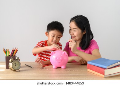 Asia Boy and His Mother with Piggy bank on  table and white wall. Child Saving Money for School Education whith copy space Concept.