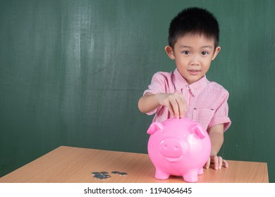 Asia Boy with Piggy bank on table and Chalkboard.Child Saving Money for School Education Concept.