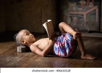 Asia boy reading a book ,sleep on bed wood with traditional Thai suit in Ayutthaya Thailand