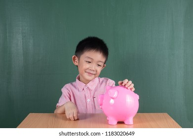 Asia Boy Smiling with Piggy bank on table and Chalkboard.Child Saving Money for School Education Concept.