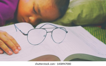 Asia boy student with books sleeping on the table. education, exams and school concept . studying hard.
