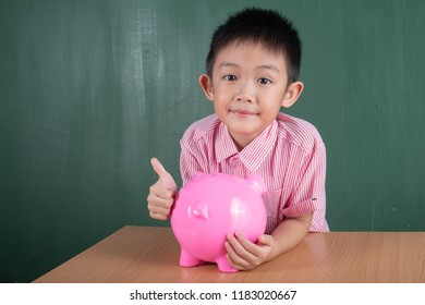Asia Boy Thumb up with Piggy bank on table and Chalkboard.Child Saving Money for School Education Concept.