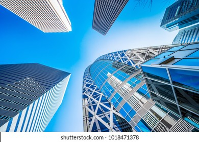 Asia Business concept for real estate and corporate construction - looking up view in financial district, the silhouettes of skyscrapers reflect blue sky in Tokyo, Japan