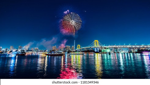 Asia Business concept for real estate and corporate construction - panoramic city skyline view of tokyo bay firework, ship and rainbow bridge under blue night sky in odaiba, Tokyo, Japan