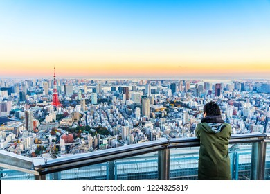 Asia Business concept for real estate and corporate construction - Tourists take shot of Tokyo Tower under bright golden sun and vivid twilight sky in Roppongi Hill, Tokyo, Japan
