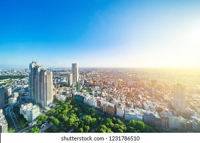 Asia Business concept for real estate and corporate construction - panoramic modern city skyline aerial view of shinjuku area under bright blue sky and sun in Tokyo, Japan