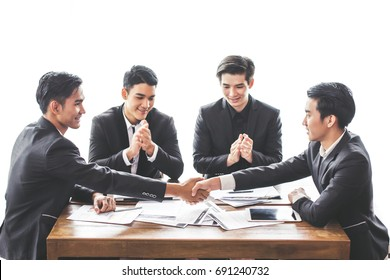 Asia business people Shake hand Cooperating relationship teamwork They smile sitting on chair at the office with her colleagues.
