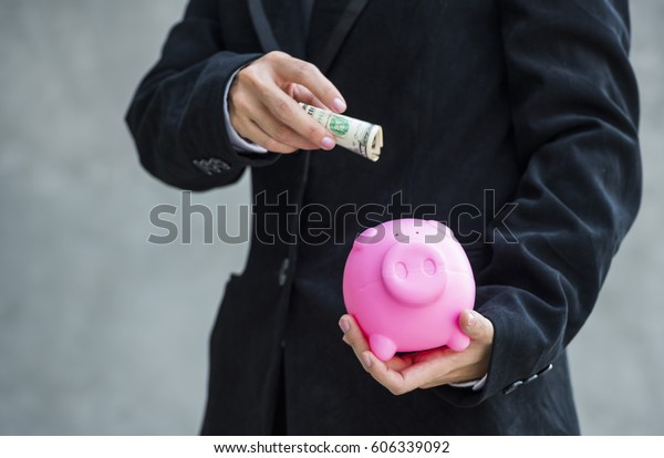 Asia business woman keeping money in piggy bank in white hand
