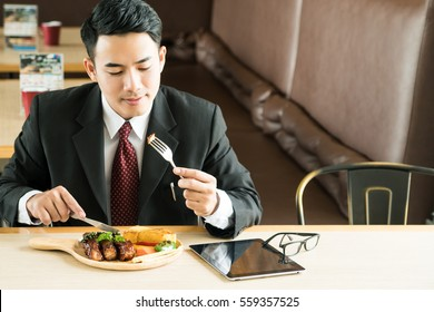 Asia businessman eating with reading news update from tablet computer.