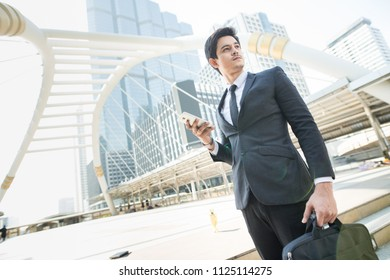 Asia Businessman Standing holding his smart phone