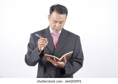 Asia businessman writing on the book