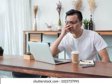 asia casual man cover face with hand upset from work in front of laptop computer in coffee shop,stress emotion concept,work outside office,work at home